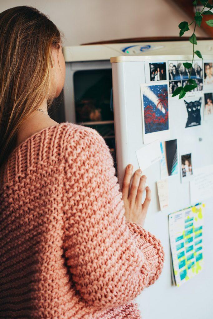 Une femme qui ouvre la porte de son frigo pour cuisiner