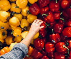 Un personne en train de choisir des poivrons rouges et jaunes