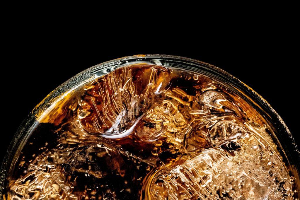 Gros plan, vu de haut, sur un verre à whisky avec des glaçons