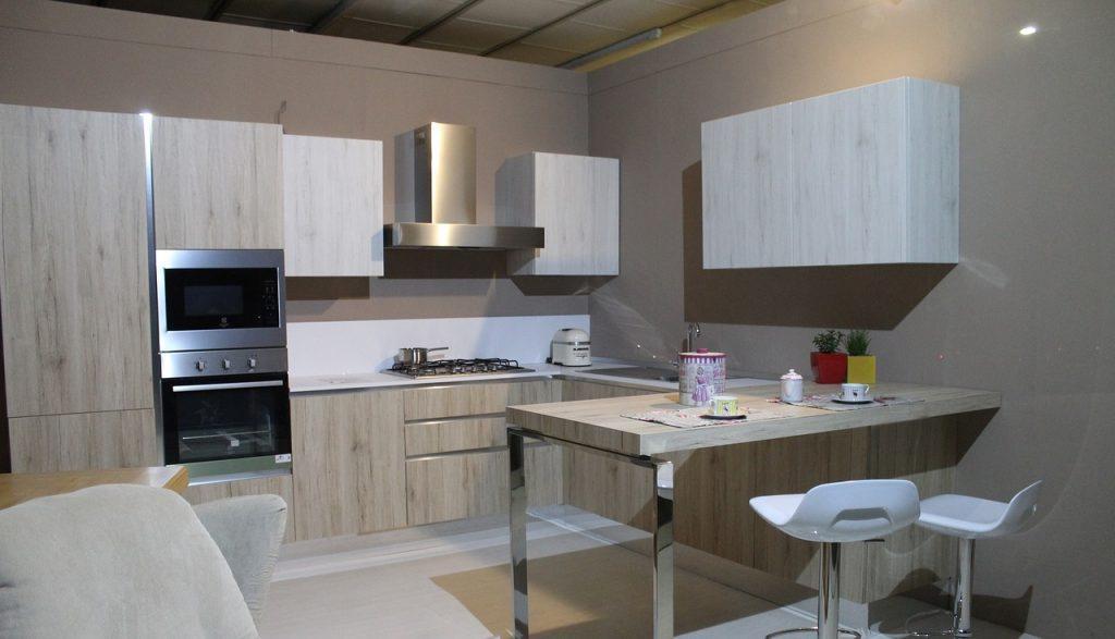 cuisine dans les tons bois clair en L avec retour table hauteur plan de travail et chaises hautes